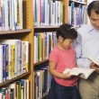 Stock Photo: Father and daughter looking at library books