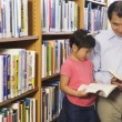 Father and daughter looking at library books - Stock Photo