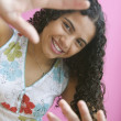 Portrait of teenage girl smiling with hands raised - Stock Photo