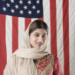Portrait of woman wearing scarf standing in front of American flag — Stock Photo