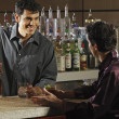 Hispanic male bartender talking to customer — Stock Photo