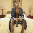 Man in robe with champagne in bedroom — Stock Photo
