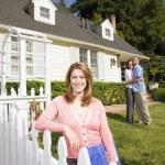 Pareja abrazándose frente a casa con el agente de bienes raíces — Foto de Stock