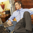 Businessman looking at laptop in bed — Foto de Stock