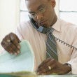 Businessman reading papers while talking on phone — Stock Photo
