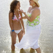 Stock Photo: Hispanic mother and daughter wading in water
