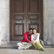 Asian couple sitting in doorway in London — Stock Photo