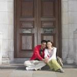 Asian couple sitting in doorway in London — Stock Photo