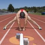 Hispanic male runner stretching on track — Stock Photo #13231078