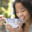 Asian woman eating with chopsticks — Stock Photo