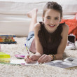 Young girl doing homework on floor - Stock Photo