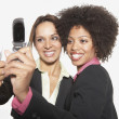 Businesswomen taking pictures of themselves with their camera phones — Stock Photo