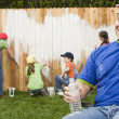 Mixed Race family painting fence — Stock Photo #13231149
