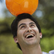 Man balancing soccer ball on head outdoors — Stock Photo