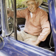 Portrait of elderly man sitting in old pickup truck — Stock Photo
