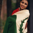 Young woman wrapped up in a national flag — Stock Photo