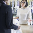 Asian drycleaner talking to customer — Stock Photo