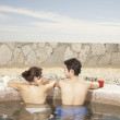 Couple in hot tub outdoors at beach resort — Stock Photo