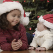Stock Photo: Hispanic girl smiling at baby sibling on Christmas