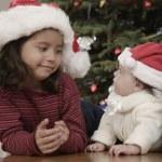 Hispanic girl smiling at baby sibling on Christmas — Stock Photo