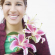Stock Photo: Young woman holding flowers