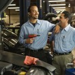 Multi-ethnic male auto mechanics in shop — Stock Photo