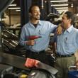 Multi-ethnic male auto mechanics in shop — Stock Photo #13231231
