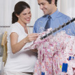 Pregnant Woman and Husband Shopping for Baby Clothes — Stock Photo