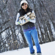 Asian woman carrying firewood in snow — Stock Photo