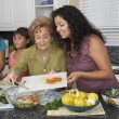 Multi-generational Hispanic female family members preparing food — Stock Photo