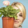 Young woman holding potted plant in front of face — Stock Photo #13231299