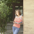 Young woman leaning against wall - Stockfoto