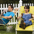 Multi-ethnic couple relaxing in lawn chairs — ストック写真