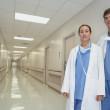 Hispanic female and male doctor standing in hospital corridor — Stock Photo