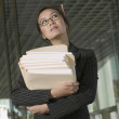 Businesswoman holding stack of paperwork — Stock Photo