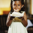 Young girl holding a piece of birthday cake — Stock Photo #13231347