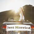 Royalty-Free Stock Photo: Bride standing in convertible with Just Married banner on the back