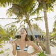 Woman laughing while using her digital camera on the beach — Stock Photo