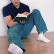 Young man sitting on a floor reading a book — Stock Photo