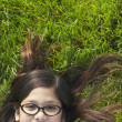 Girl wearing glasses lying in grass — Stock Photo
