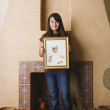 Hispanic teenaged girl holding baby photograph - Stock Photo
