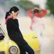 Stock Photo: Womtalking on cell phone about car breakdown