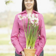 Portrait of Hispanic woman holding potted plant — Stock Photo