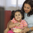 Mother and daughter watching television and eating popcorn — Stock Photo