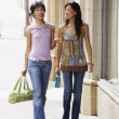 Two women walking on sidewalk — Stock Photo