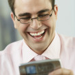 Middle Eastern businessman laughing at cell phone — Stock Photo #13231453