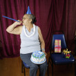 Woman with party favors and birthday cake — Stock Photo
