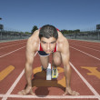 图库照片: Male track athlete at starting line