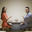 Asian couple kneeling having tea — Stock Photo #13231535