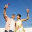 Multi-ethnic couple holding cocktails — Stock Photo #13231565